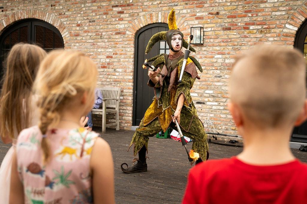 Nar jongleert met fakkels op kinderfeestje